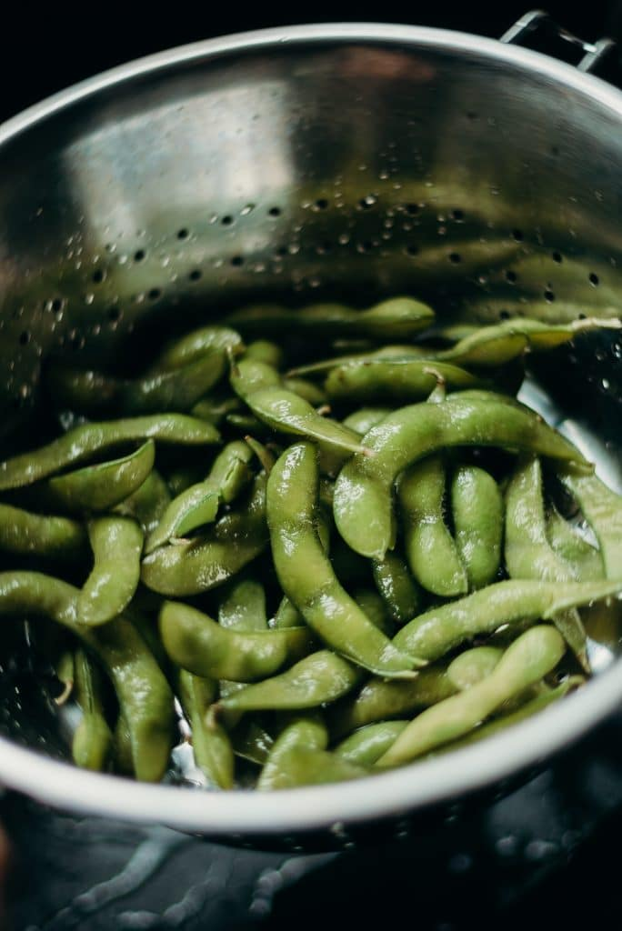 edamame beans in a strainer in a sink