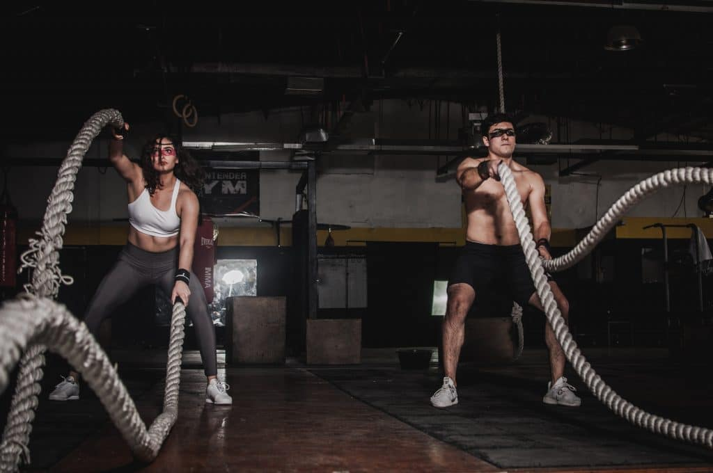 man and woman using ropes to workout