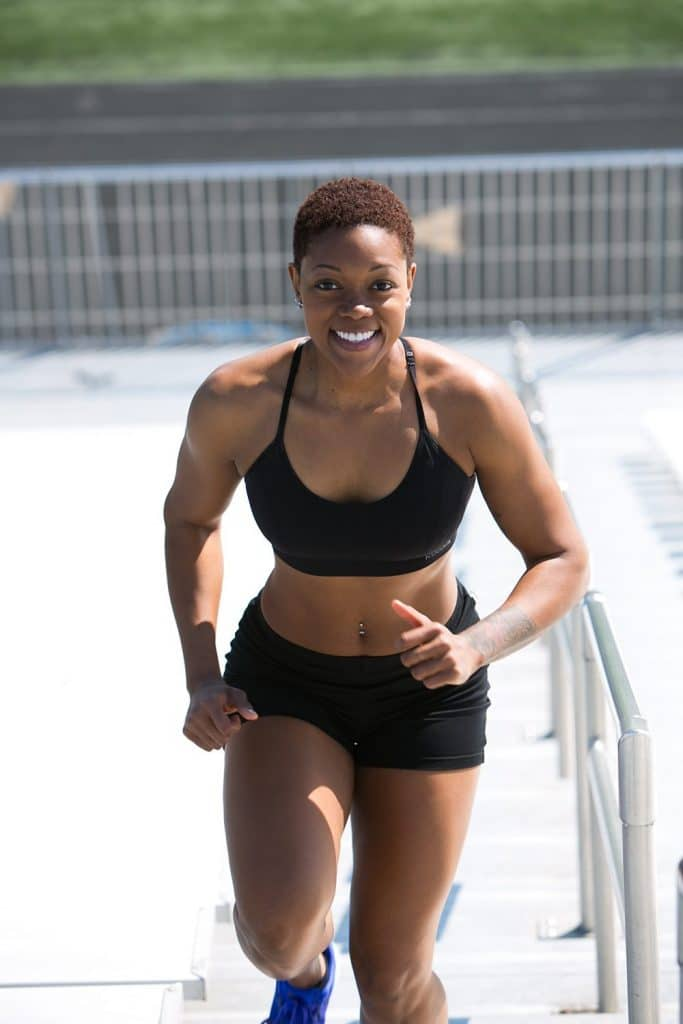 woman running up stadium stairs to exercise