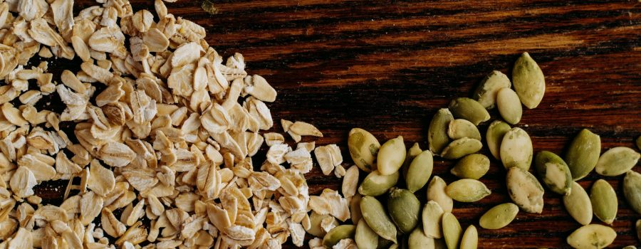 oats and pumpkin seeds on a wooden background