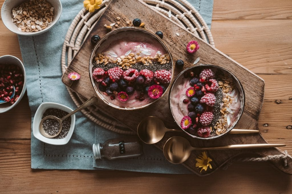 bowls of oatmeal with fresh berries on a wooden board