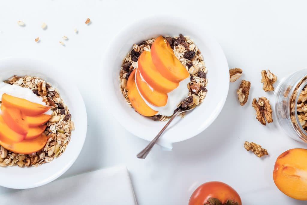 two bowls of muesli with sliced persimmons and vegan yogurt