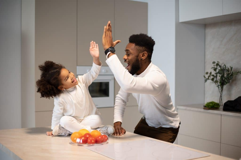 father and daughter high-fiving in a kitchen with a bowl of colorful fruits and vegetables