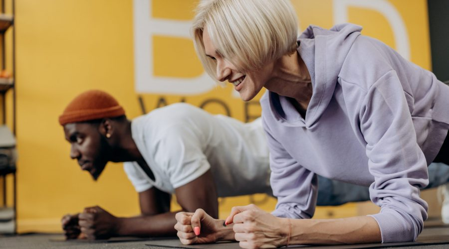 a woman and a man doing planks at a workout gym with high energy