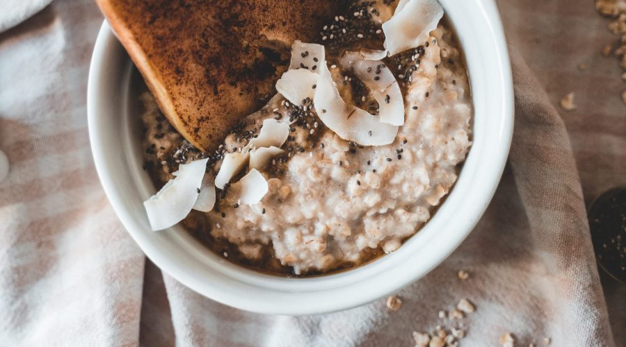 bowl of hot muesli porridge with a cinnamon roasted pear and coconut flakes