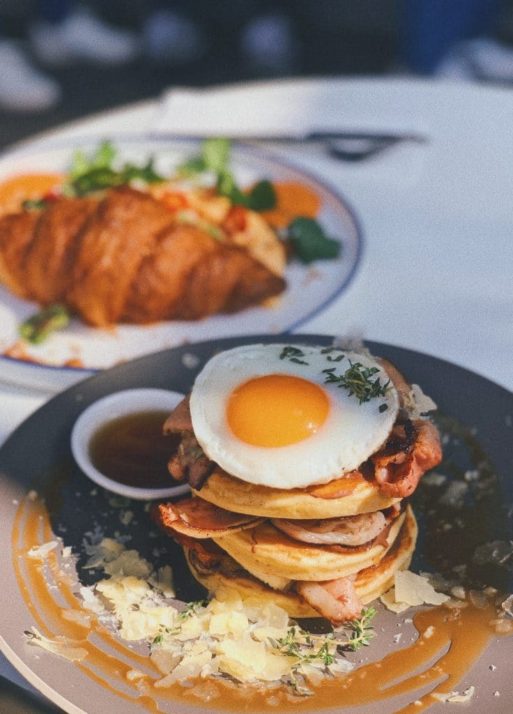 stack of pancakes with bacon, egg and cheese on top