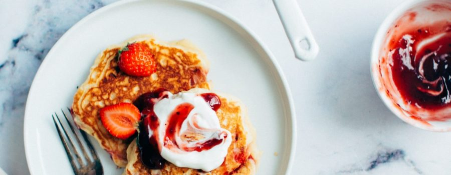 plate of pancakes with berries and whipped cream on top